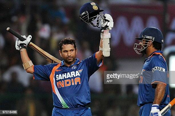 Indian cricketer Sachin Tendulkar raises his hat and helmet to celebrate scoring a world record breaking double century during the second One Day...