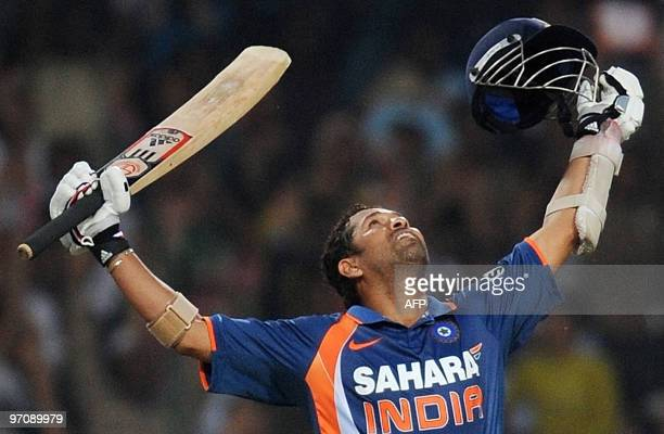 Indian cricketer Sachin Tendulkar throws his arms up into the air as he celebrates scoring a world record breaking double century during the second...