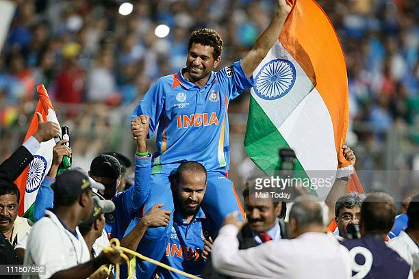 Indian cricketer Sachin Tendulkar waves the Indian Tricolour celebrating their team's victory during the ICC Cricket World Cup final match between...