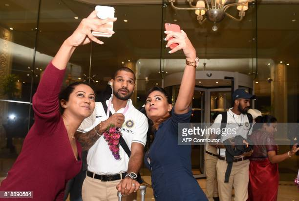 Indian cricketer Shikar Dhawan poses for a 'selfie' as he and teammates arrive at a hotel in Colombo on July 19 2017 India and Sri Lanka will play...