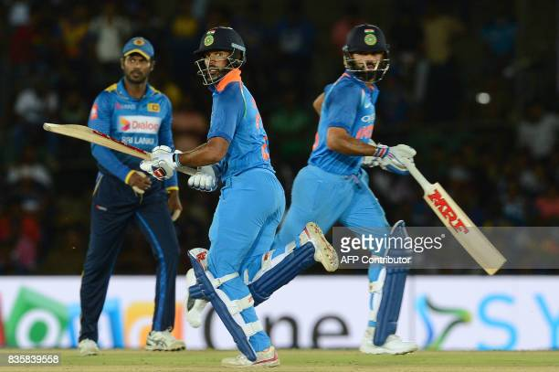 Indian cricketer Shikhar Dhawan and captain Virat Kohli run between the wickets during the first One Day International cricket match between Sri...