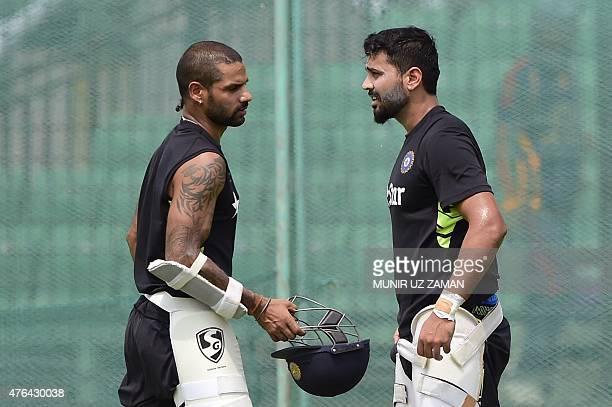 Indian cricketer Shikhar Dhawan and Murali Vijay talk during a practice session at Khan Shaheb Osman Ali Stadium in Narayanganj on June 9 ahead of...