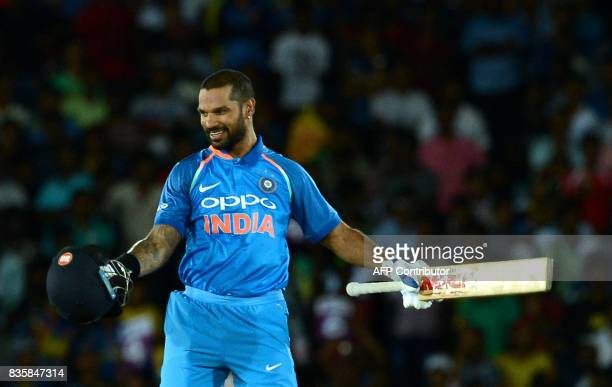 Indian cricketer Shikhar Dhawan celebrates after he scored a century during the first One Day International cricket match between Sri Lanka and India...