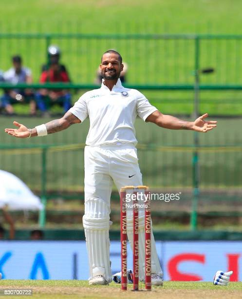 Indian cricketer Shikhar Dhawan celebrates after scoring 100 runs during the 1st Day's play in the 3rd Test match between Sri Lanka and India at the...