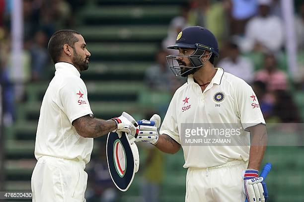 Indian cricketer Shikhar Dhawan celebrates with teammate Murali Vijay after scoring a century during the first day of the first cricket Test match...