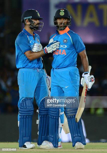 Indian cricketer Shikhar Dhawan is congratulated by his captain Virat Kohli after scoring a halfcentury during the first One Day International...