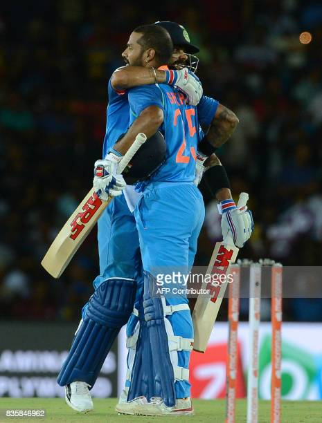 Indian cricketer Shikhar Dhawan is congratulated by his captain Virat Kohli after he scored a century during the first One Day International cricket...