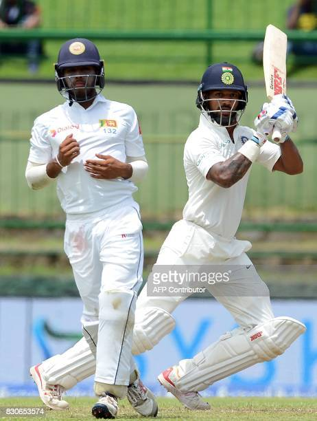Indian cricketer Shikhar Dhawan is watched by Sri Lankan cricketer Kusal Mendis as he plays a shot during the first day of the third and final Test...