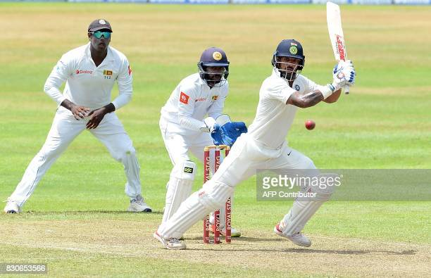 Indian cricketer Shikhar Dhawan is watched by Sri Lankan wicketkeeper Niroshan Dickwella as he plays a shot during the first day of the third and...