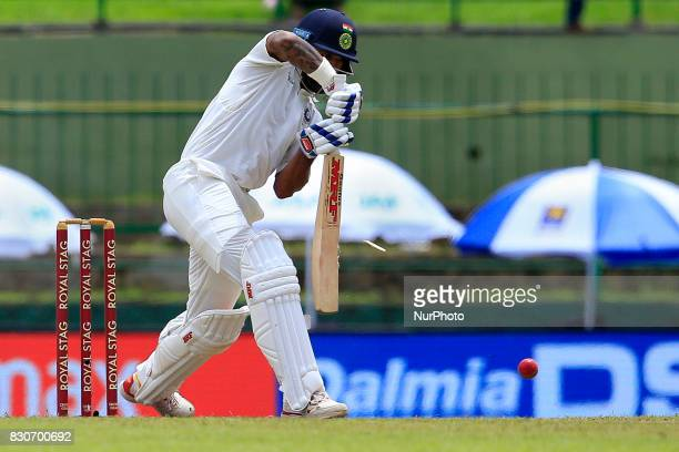 Indian cricketer Shikhar Dhawan plays a shot as a part of his bat brakes during the 1st Day's play in the 3rd Test match between Sri Lanka and India...