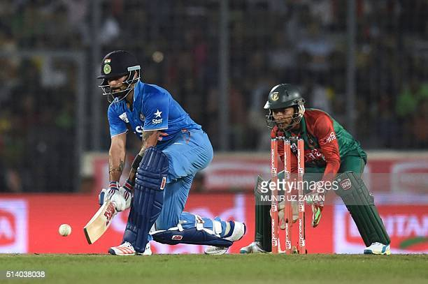 Indian cricketer Shikhar Dhawan plays a shot as Bangladeshi wicketkeeper Mushfiqur Rahim looks on during the Asia Cup T20 cricket tournament final...