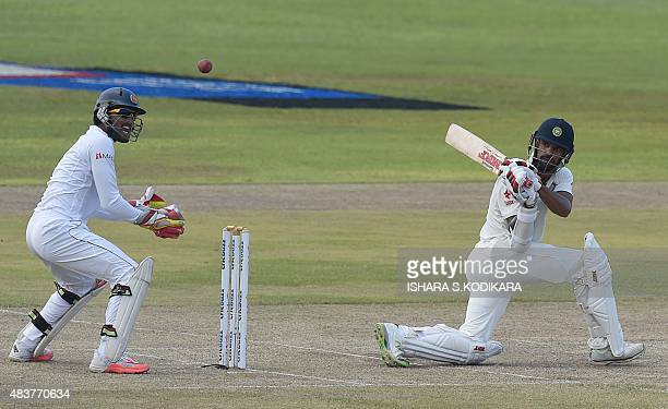 Indian cricketer Shikhar Dhawan plays a shot as Sri Lankan wicketkeeper Dinesh Chandimal looks on during the second day of the opening Test match...