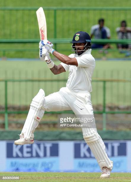 Indian cricketer Shikhar Dhawan plays a shot during the first day of the third and final Test match between Sri Lanka and India at the Pallekele...