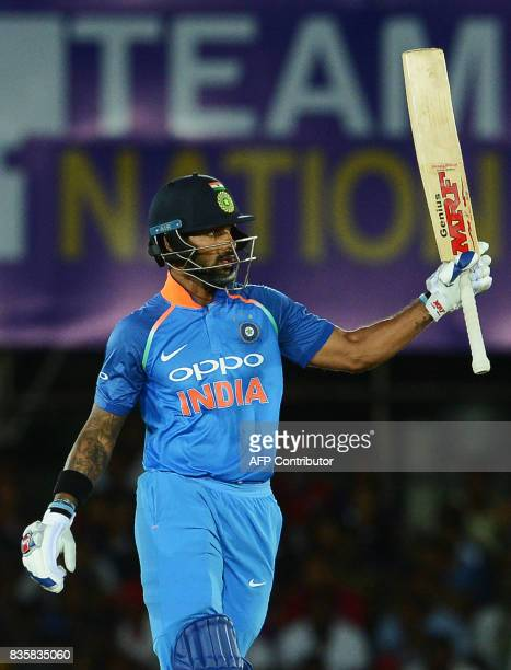 Indian cricketer Shikhar Dhawan raises his bat to the crowd after scoring a halfcentury during the first One Day International cricket match between...