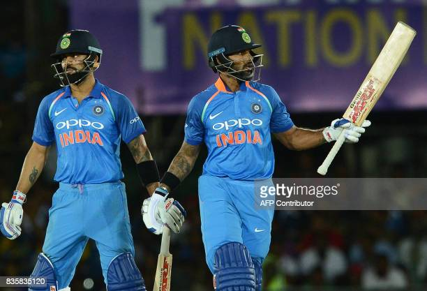 Indian cricketer Shikhar Dhawan raises his bat to the crowd next to his captain Virat Kohli after scoring a halfcentury during the first One Day...