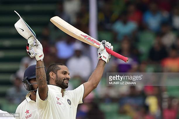 Indian cricketer Shikhar Dhawan reacts after scoring a century during the first day of the first cricket Test match between Bangladesh and India at...