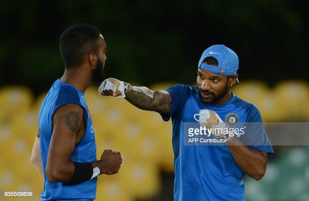 Indian cricketer Shikhar Dhawan shares a light moment with teammate Lokesh Rahul during a practice session at the Rangiri Dambulla International...