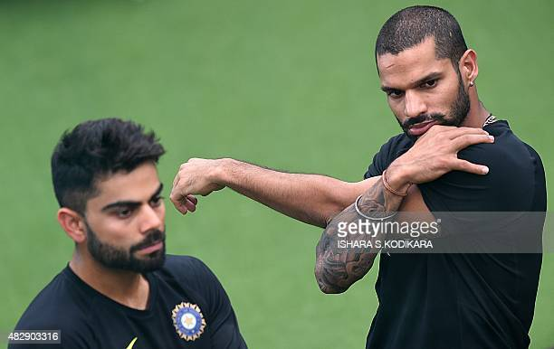 Indian cricketer Shikhar Dhawan stretches as captain Virat Kohli looks on during a net practice session at the National Cricket Club in Colombo on...