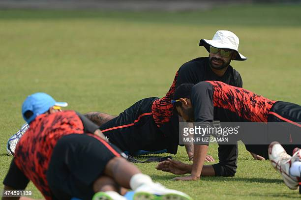 Indian cricketer Shikhar Dhawan stretches during a team training session at the ShereBangla National Cricket Stadium in Dhaka on February 24 2014 AFP...