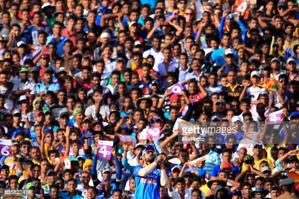 Indian cricketer Shikhar Dhawan takes a catch as spectators look on during the 1st One Day International cricket match bewtween Sri Lanka and India...