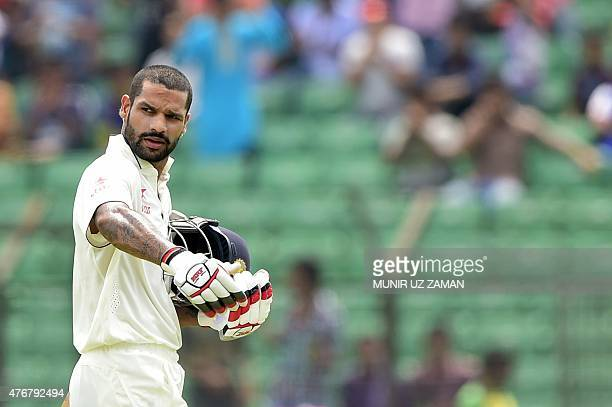 Indian cricketer Shikhar Dhawan walks off the field following his dismissal by Bangladesh cricketer Shakib Al Hasan during the third day of the Test...