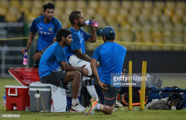 Indian cricketer Shikhar Dhawan with teammates takes a rest during a practice session at The RPeremadasa Stadium in Colombo on August 30 2017 The...