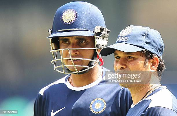 Indian Cricketer Sourav Ganguly talks with teammate Sachin Tendulkar during a practice session at the Chinnaswamy Stadium in Bangalore on October 7...