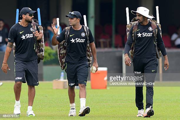Indian cricketer Stuart Binny and teammates Murali Vijay and Cheteshwar Pujara walk with equipment during a practice session at the P Sara Oval...