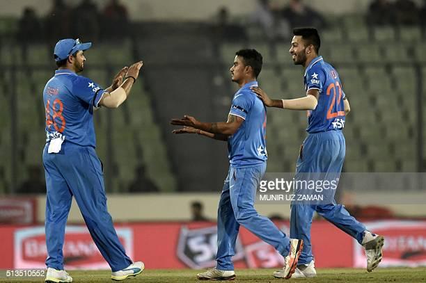 Indian cricketer Suresh Raina and Hardik Pandya congratulate teammate Pawan Neg after the dismissal of unseen United Arab Emirates batsman Fahad...