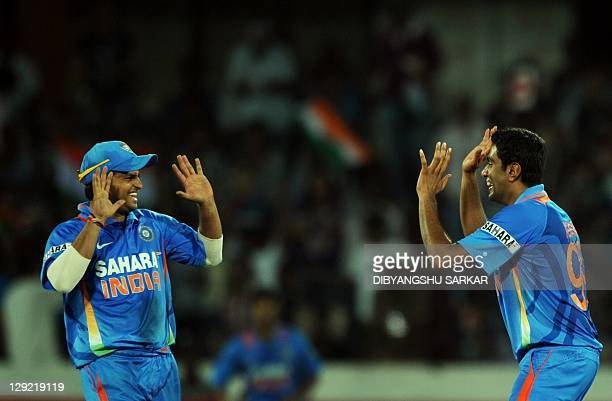 Indian cricketer Suresh Raina congratulates teammate Ravichandran Ashwin for taking the wicket of unseen England batsman Ravi Bopara during during...