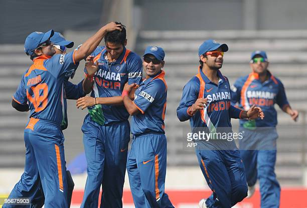 Indian cricketer Suresh Raina congratulates teammate Sudeep Tyagi during the TriNation tournament One Day International cricket match at The Shere...
