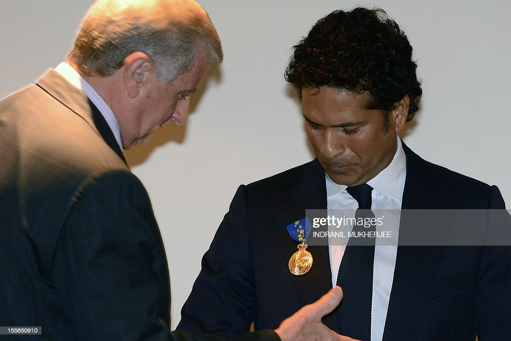Indian cricketer Tendulkar looks at his medal after being conferred with the membership of The Order of Australia by Simon Crean (L), Australian Minister for Regional Australia, Regional Development and Local Government, during a ceremony in Mumbai on November 6, 2012. India's record-breaking batsman Sachin Tendulkar on November 6 was conferred with membership of the Order of Australia. Australian Prime Minister Julia Gillard, who announced Tendulkar's membership to the Order during a three-day state visit to India last month, told reporters that Tendulkar deserved the 'special honour' because he was a 'very special cricketer'. AFP PHOTO/ INDRANIL MUKHERJEE