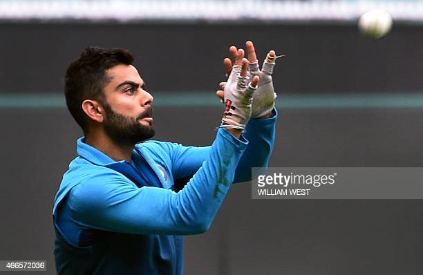 Indian cricketer Virat Kohli takes a catch during a training session ahead of their 2015 Cricket World Cup quarterfinal match against Bangladesh in...