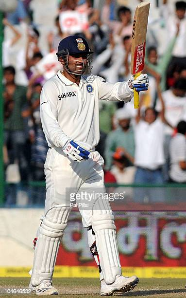 Indian cricketer Virender Sehwag raises his bat after scoring a half century during day two of the First Test match between India and Australia at...