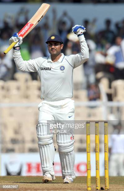 Indian cricketer Virender Sehwag raises the bat after scoring a century during play on the second day of the third Test match between India and Sri...