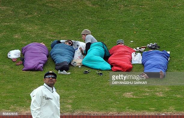 Indian cricketer Virender Sehwag stands next to spectators taking rest during the final day of the final Test match between New Zealand and India at...