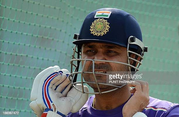 Indian cricketer Virender Sehwag wears his helmet as he prepares to bat in the nets during a training session at The Sardar Patel Stadium at Motera...