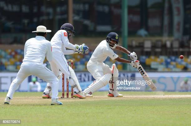 Indian cricketer Wriddhiman Saha is watched by Sri Lankan wicketkeeper Niroshan Dickwella as he plays a shot during the second day of the second Test...