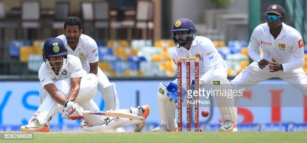 Indian cricketer Wriddhiman Saha plays a shot as Sri Lanka's Dimuth KarunarathneNiroshan Dickwella and Angelo Mathews look on during the 2nd Day's...