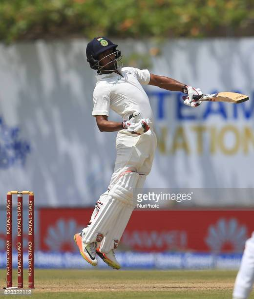 Indian cricketer Wriddhiman Saha reacts as he leaves a bouncer ball during the 2nd Day's play in the 1st Test match between Sri Lanka and India at...