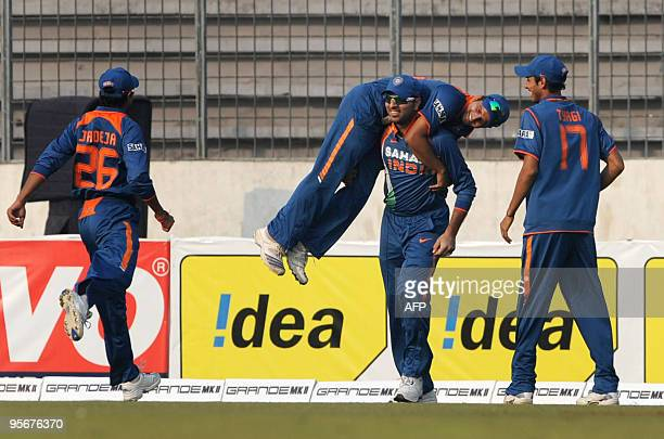 Indian cricketer Yuvraj Singh lifts his team mate Suresh Raina as cricketers Ravindra Jadeja and Sudeep Tyagi look on after the dismissal of Sri...