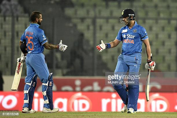 Indian cricketer Yuvraj Singhshakes hands with teammate Shikhar Dhawan as they celebrates after winning the Asia Cup T20 cricket tournament match...