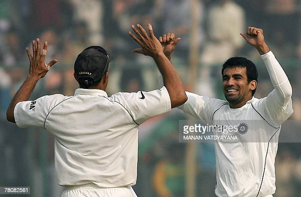 Indian cricketer Zaheer Khan celebrates with captain Anil Kumble after taking the wicket of Pakistan's Sohail Tanveer during the fourth day of the...