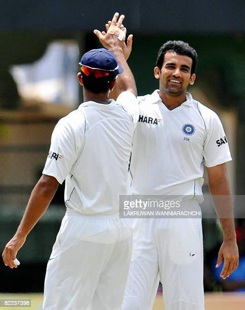 Indian cricketer Zaheer Khan celebrates with teammate Rahul Dravid the dismissal of unseen Sri Lankan batsman Prasana Jayawerdane during the third...