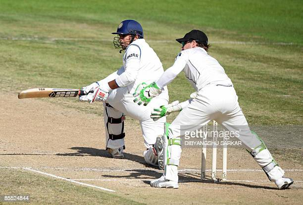 Indian cricketer Zaheer Khan plays a shot as New Zealand wicketkeeper Brendon McCullum looks on during the third day of the first Test match between...