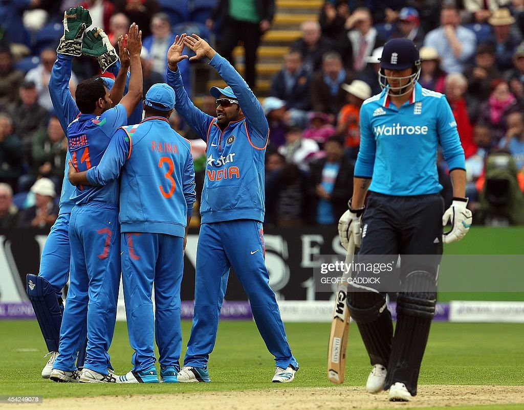 Indian cricketers celebrate as England's Alastair Cook (R) leaves the field after being dismissed lbw by India's Mohammed Shami during the second one-day international cricket match between England and India at the Glamorgan County Cricket Ground in Cardiff, Wales on August 27, 2014.