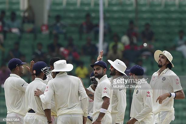 Indian cricketers celebrate the dismissal of Bangladesh captain Mushfiqur Rahim during the fourth day of the Test match between Bangladesh and India...