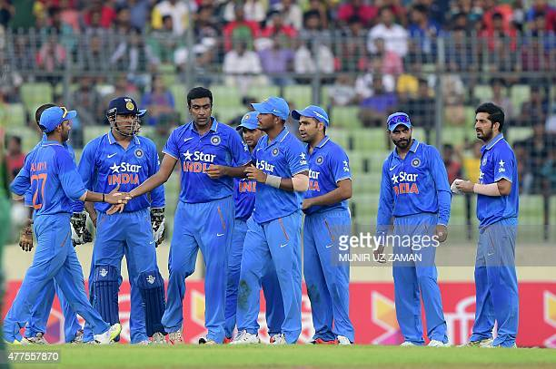 Indian cricketers congratulate teammate Ravichandran Ashwin after the dismissal of Bangladesh cricketer Mushfiqur Rahim during the first One Day...