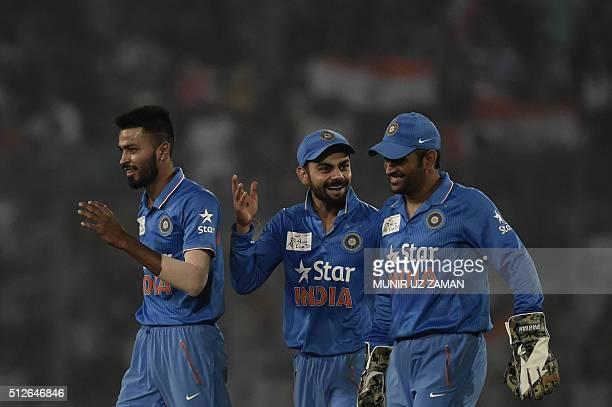 Indian cricketers Hardik Pandya and Virat Kohli and captain Mahendra Singh Dhoni react after the dismissal of the Pakistan cricketer Mohammad Sami...