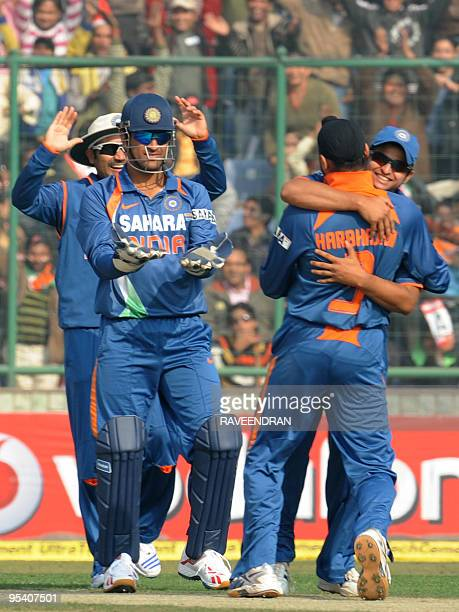 Indian cricketers led by captain Mahendra Singh Dhooni celebrate the dismissal of unseen Sri Lankan batsman Sanath Jayasuriya during the fifth and...